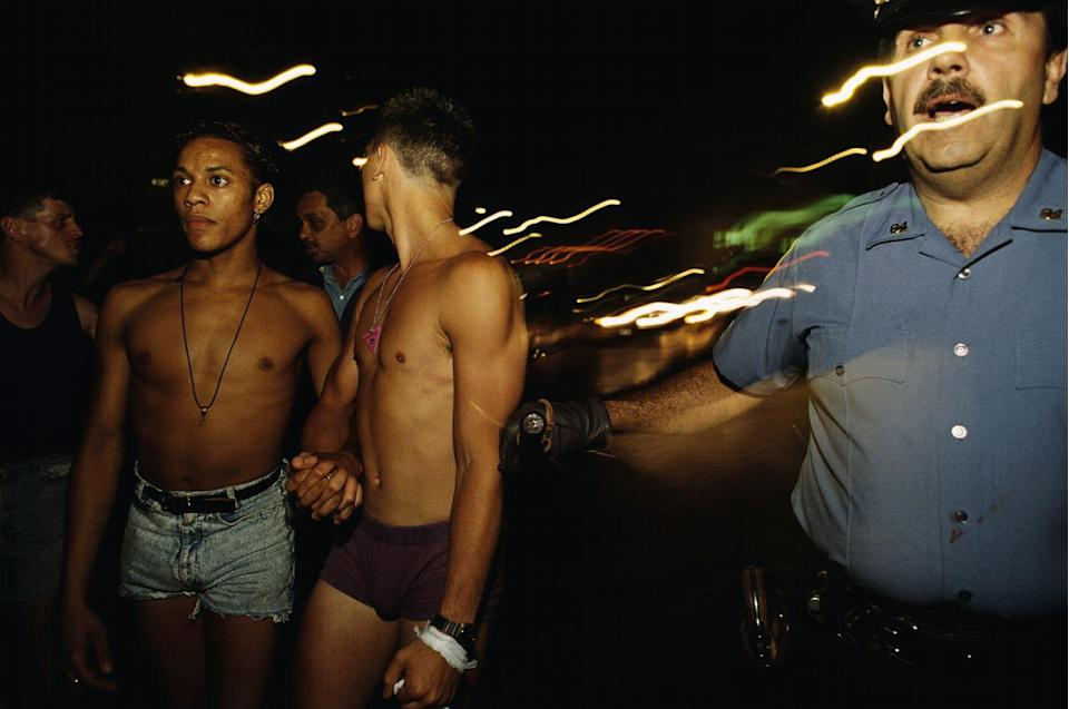 <p>Young guys hold hands as they're escorted during the 25th anniversary of the Stonewall Uprising in New York City. <br></p>
