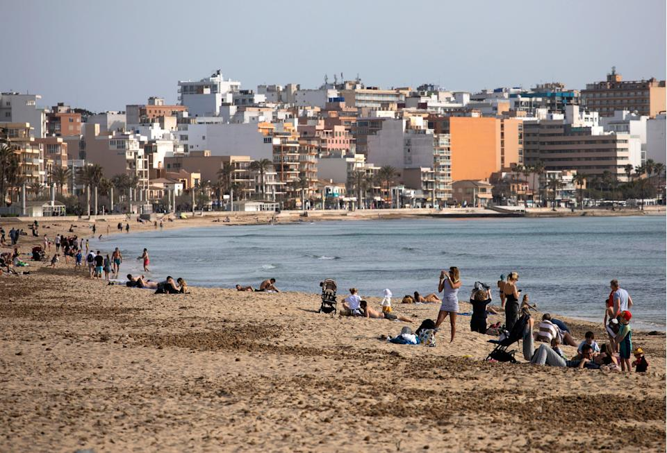 <p>Tourists enjoy the beach at the Spanish Balearic Island of Mallorca</p> (AP)