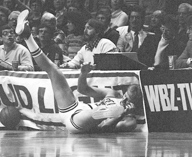 Larry Bird slides head first under the scorer's table after a loose ball during the first half of a mid-January Celtics-Pacers game in 1984. (AP)