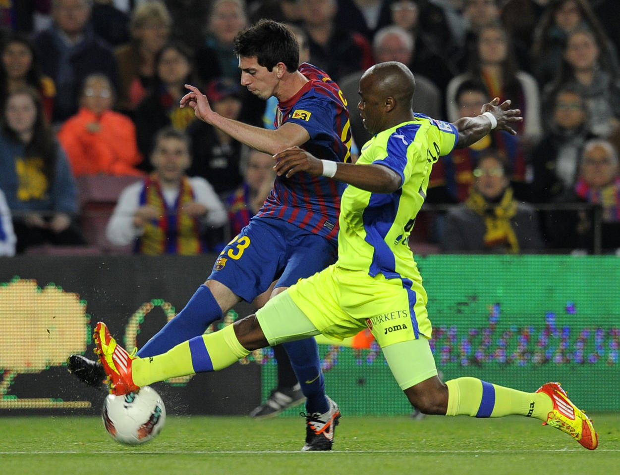 Barcelona's forward Isaac Cuenca (L) vies with Getafe's South African defender Tshepo Masilela (R) during the Spanish league football match FC Barcelona vs Getafe CF on April 10, 2012 at the Camp Nou stadium in Barcelona. AFP PHOTO/LLUIS GENE (Photo credit should read LLUIS GENE/AFP/Getty Images)