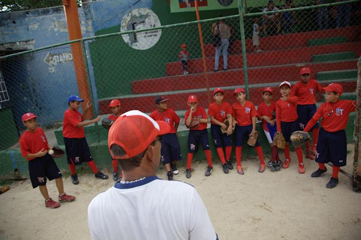 In this Oct. 25, 2012 photo, boys attend a baseball school in Maracay, Venezuela. Many of the boys are inspired by the example of Detroit Tigers slugger Miguel Cabrera, who learned the game on this very field. Their baseball school in the poor neighborhood where Cabrera grew up is one of many across Venezuela, a web for training young ballplayers that has made the country a powerhouse in the U.S. major leagues. (AP Photo/Ariana Cubillos)