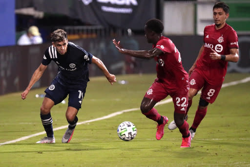 New York City FC forward Jesus Medina (19) works past Toronto FC midfielder Richie Laryea (22) and midfielder Marco Delgado (8) during the first half of an MLS soccer match, Sunday, July 26, 2020, in Kissimmee, Fla. (AP Photo/John Raoux)