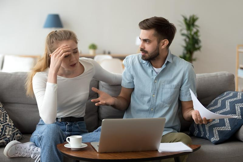 Stressed unhappy couple arguing about huge expenses with laptop and papers, angry husband blaming wife of overspending debt, family having conflict fight about wasting money financial problem at home