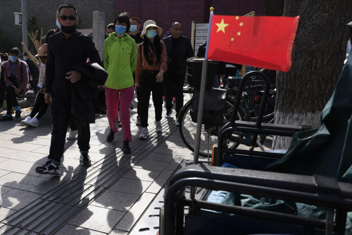 Residents in masks pass a Chinese national flag outside the Forbidden City where a bus is offering free coronavirus vaccinations in Beijing on Wednesday, April 14, 2021. China's success at controlling the outbreak has resulted in a population that has seemed almost reluctant to get vaccinated. It is now accelerating its inoculation campaign by offering incentives — free eggs, store coupons and discounts on groceries and merchandise — to those getting a shot. (AP Photo/Ng Han Guan)