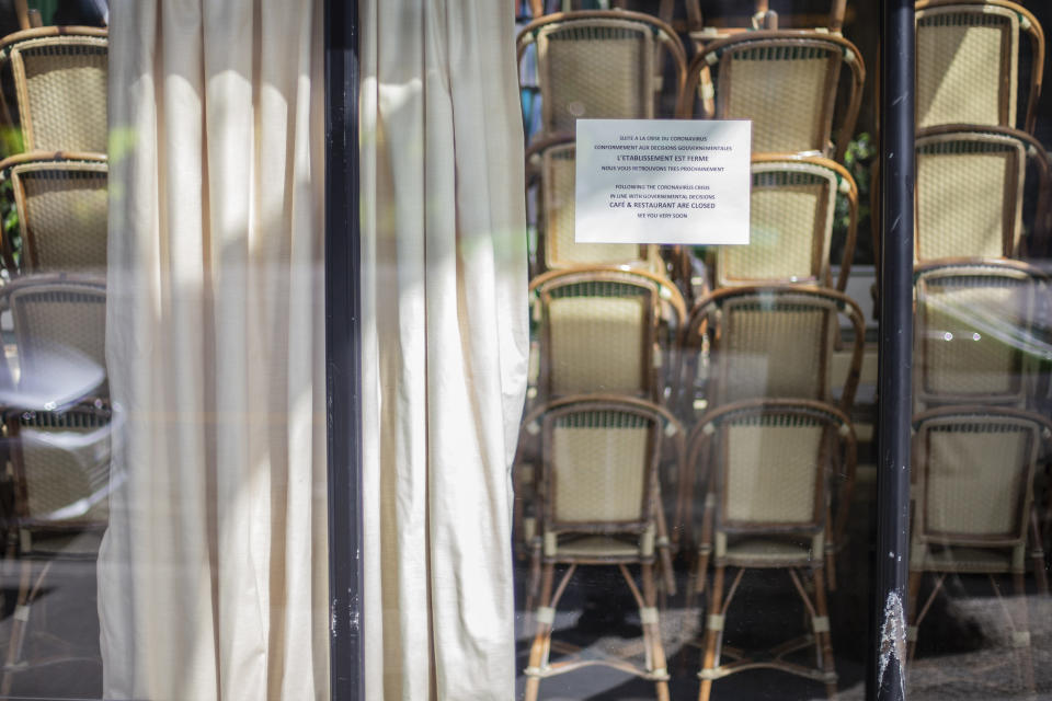 Chairs pile up behind the window of the famed Les Deux Magots cafe Sunday March 15, 2020 in Paris. French Prime Minister Edouard Philippe announced that France is shutting down all restaurants, cafes, cinemas and non-essential retail shops, starting Sunday, to combat the accelerated spread of the virus in the country. . For most people, the new coronavirus causes only mild or moderate symptoms. For some it can cause more severe illness. (AP Photo/Rafael Yaghobzadeh)