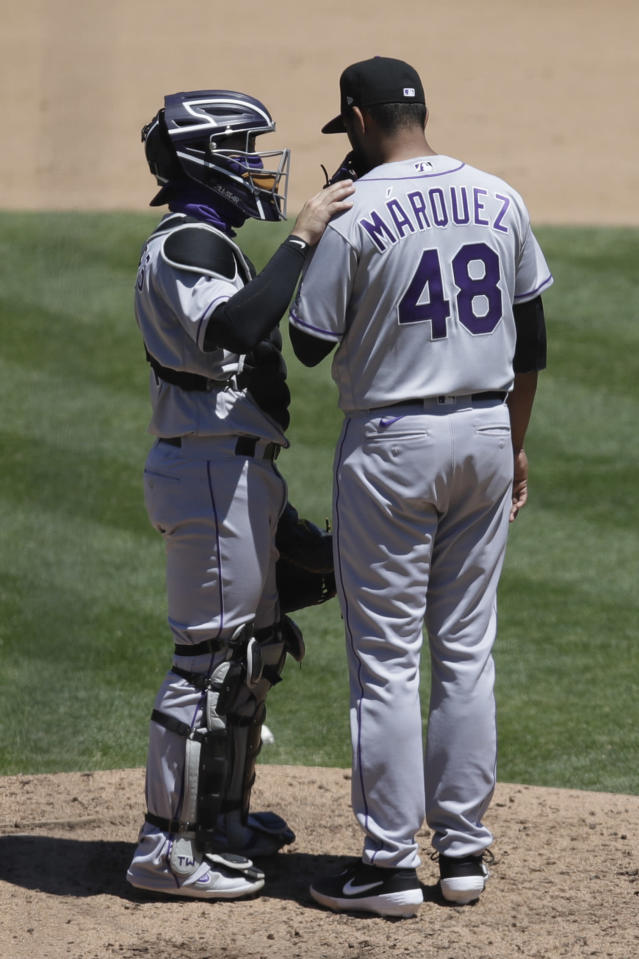 Colorado Rockies' Tony Wolters, left, speaks with pitcher German Marquez (48) during the fifth inning of a baseball game against the Oakland Athletics Wednesday, July 29, 2020, in Oakland, Calif. (AP Photo/Ben Margot)