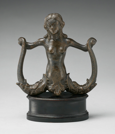 A bronze statue of a mermaid with two tails. She is holding a tail in each hand.