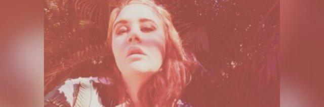 selfie author took with a red tint, eyes looking up, and her hand on the side of her head