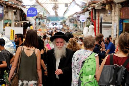 An ultra-Orthodox Jewish man (C) looks ahead as he walks through a market in Jerusalem May 11, 2017. Picture taken May 11, 2017. REUTERS/Amir Cohen