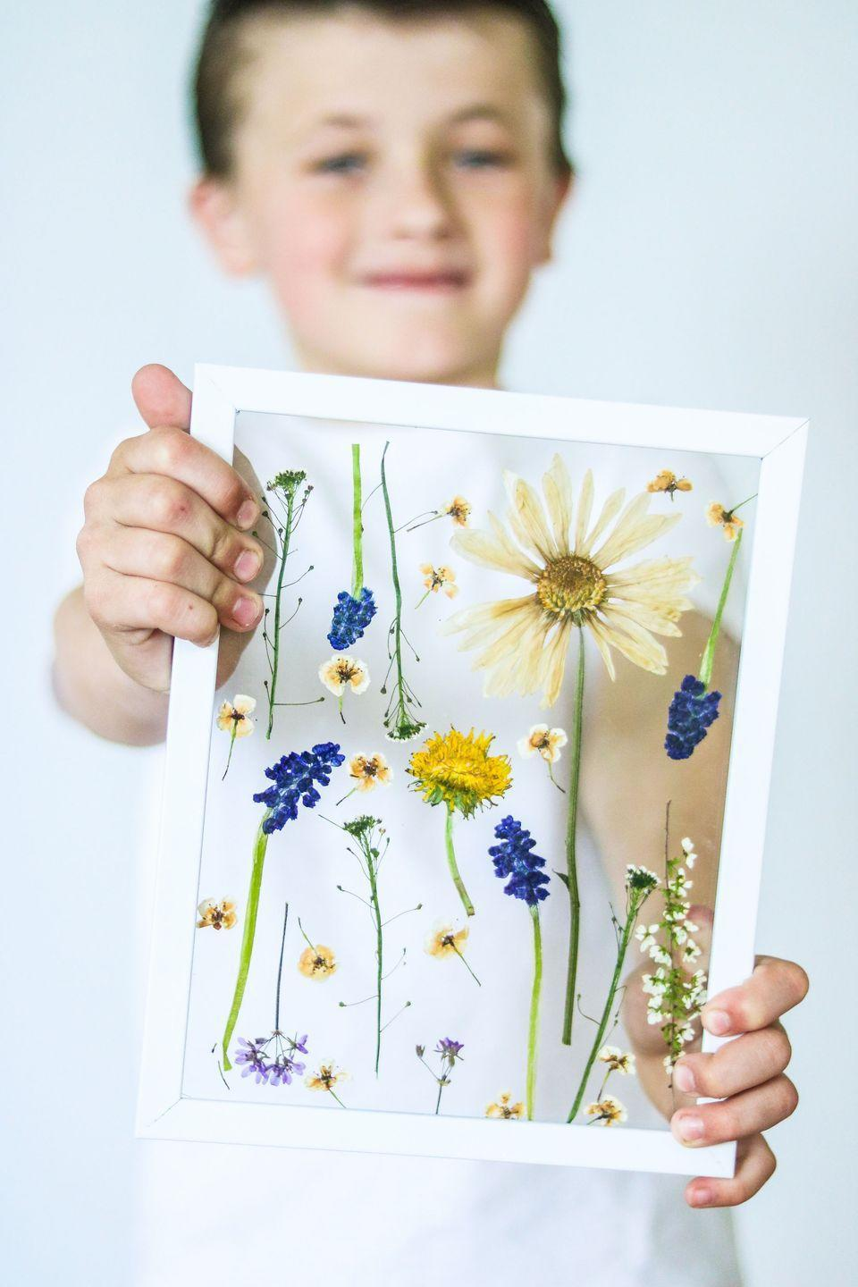 """<p>Flatten real flowers—or even weeds!—from your garden to make a one-of-a-kind Mother's Day craft. It will look especially beautiful hanging near a window with the sunlight shining through.</p><p><strong>Get the tutorial at <a href=""""https://www.lilyardor.com/how-to-press-flowers-quick/"""" rel=""""nofollow noopener"""" target=""""_blank"""" data-ylk=""""slk:Lily Ardor"""" class=""""link rapid-noclick-resp"""">Lily Ardor</a>.</strong><br></p><p><strong>What you'll need: </strong><em>cotton fabric ($3 per yard <a href=""""https://www.amazon.com/Muslin-Fabric-Natural-Cotton-Inches/dp/B01AVOIB14"""" rel=""""nofollow noopener"""" target=""""_blank"""" data-ylk=""""slk:amazon.com"""" class=""""link rapid-noclick-resp"""">amazon.com</a>); white picture frame ($8, <a href=""""https://www.amazon.com/RPJC-Picture-Definition-Display-mounting/dp/B06Y2HNDXQ"""" rel=""""nofollow noopener"""" target=""""_blank"""" data-ylk=""""slk:amazon.com"""" class=""""link rapid-noclick-resp"""">amazon.com</a>)</em></p>"""