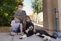 Christie Black, middle, with her two children, Angela and Luke, left, and the family dog Teddy, pose at their home, Tuesday, May 11, 2021, in Mesa, Ariz. The students, a third grader and a kindergartner, attend a school where mask wearing is optional. (AP Photo/Ross D. Franklin)