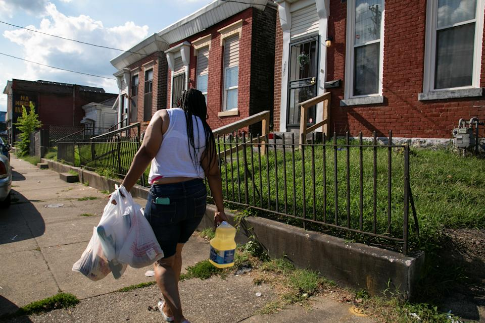 Chaunda Lee, a single mother of eight who has five children living with her, carries groceries home to make dinner for her kids, in Louisville, Kentucky, U.S. August 19, 2021. Lee was granted a reprieve from her eviction as the extended CDC moratorium was applied to her case, despite the landlord saying in court that she hadn't paid rent for six months after the two months rent free she offered her. REUTERS/Amira Karaoud