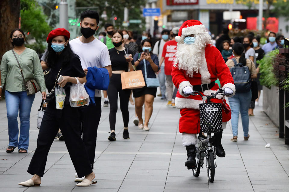 SINGAPORE - DECEMBER 24: A man dressed as Santa Claus wears a protective mask as he rides and greets shoppers along the Orchard Road shopping belt on December 24, 2020 in Singapore. As Singapore prepares to further ease COVID-19 restrictions from December 28, the government reported its first COVID-19 case carrying the potentially more contagious strain of the virus circulating in the United Kingdom yesterday. As of 24 December, the Ministry of Health confirmed 13 new imported COVID-19 cases in the wider community bringing the country's total to 58,495. (Photo by Suhaimi Abdullah/Getty Images)