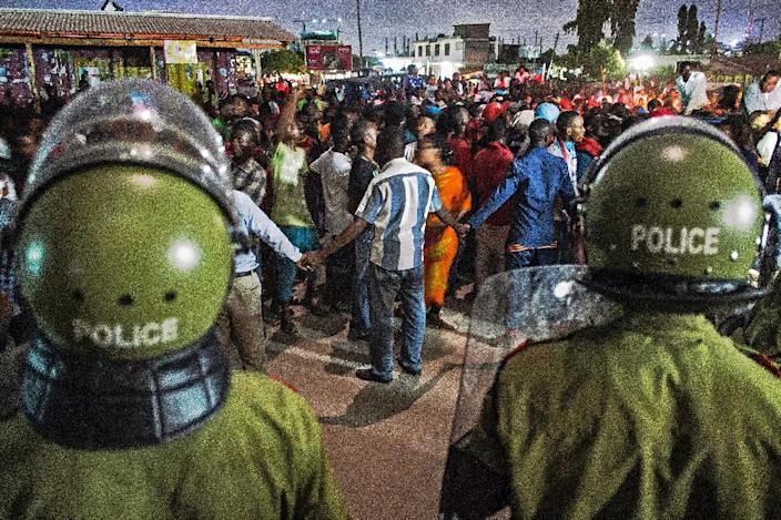 Tanzanian riot police stand guard as people celebrate after the opposition coalition's Civic United Front (CUF) candidate Maulid Mtulia was declared winner of the Kinondoni constituency in Dar es Salaam on October 28, 2015 (AFP Photo/Daniel Hayduk)
