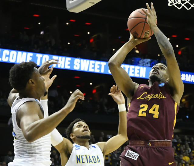 Loyola-Chicago forward Aundre Jackson (24) shoots against Nevada guard Jordan Caroline, left, and Nevada guard Hallice Cooke (13) during the first half. (AP Photo/John Amis)