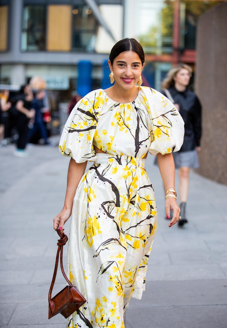 Bettina Looney is seen wearing yellow white dress with graphic print, brown bag outside Ports 1961. [Photo: Getty]