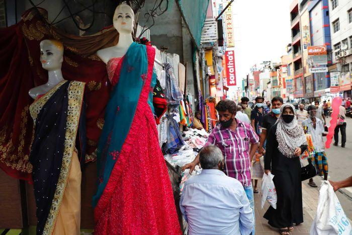 A woman wearing a burqa walks past a busy garment and textile market along a main shopping road.