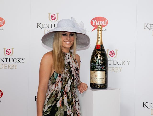"LOUISVILLE, KY - MAY 05: Red Carpet/Celebrity Signing Moment: Olympic Skier Lindsey Vonn signs a limited edition 6 Liter Moet & Chandon Imperial bottle for the brands philanthropic initiative ""Sign for the Roses"", on the red carpet at the 138th Kentucky Derby on May 5, 2012 in Louisville, Kentucky. (Photo by Joey Foley/Getty Images for Moet)"