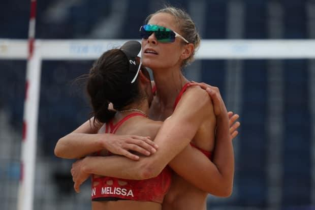 Canadian duo Melissa Humana-Paredes, left, and Sarah Pavan celebrate after earning a straight-sets (21-13, 24-22) victory over Switzerland's Joana Heidrich and Anouk Vergé-Dépré on Thursday in Tokyo. (Sean M. Haffey/Getty Images - image credit)
