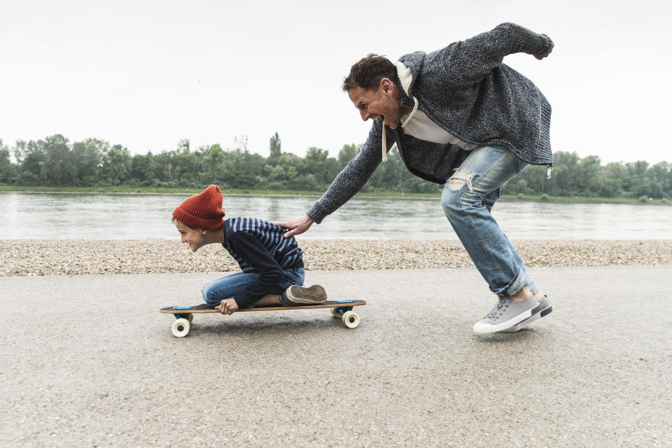 Dad and son skateboard