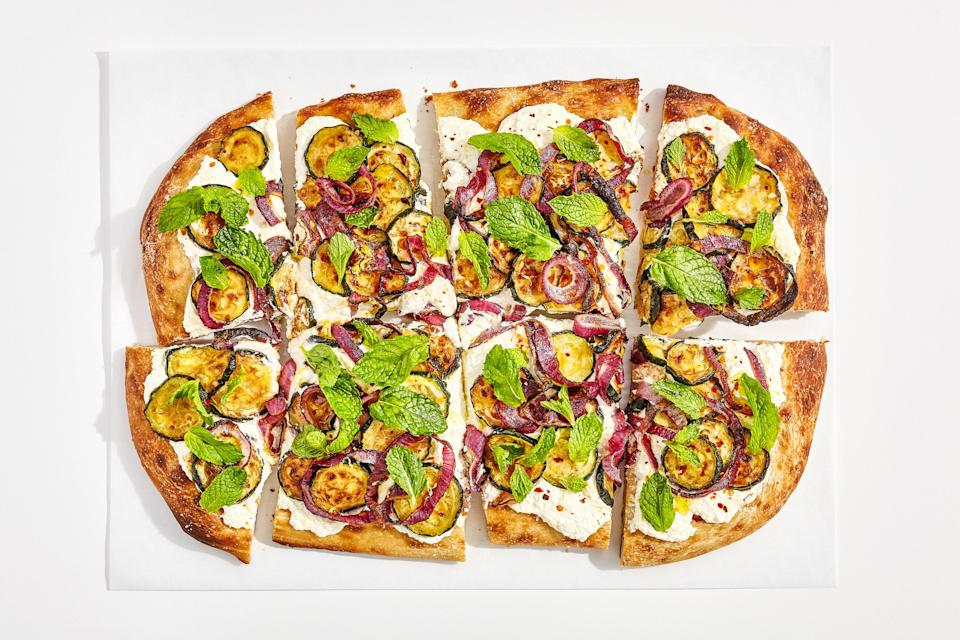 """The secret to a flatbread with a super-crunchy crust? Pre-roasting all of the veggies. This step concentrates their flavor, and also helps to cook out some of their moisture, which would otherwise soak into the crust. When shaping the dough, don't be afraid to stretch it as thinly as possible—if the dough is springing back on you, just be patient and let it rest for a few minutes. <a rel=""""nofollow noopener"""" href=""""https://www.bonappetit.com/recipe/caramelized-zucchini-flatbread?mbid=synd_yahoo_rss"""" target=""""_blank"""" data-ylk=""""slk:See recipe."""" class=""""link rapid-noclick-resp"""">See recipe.</a>"""