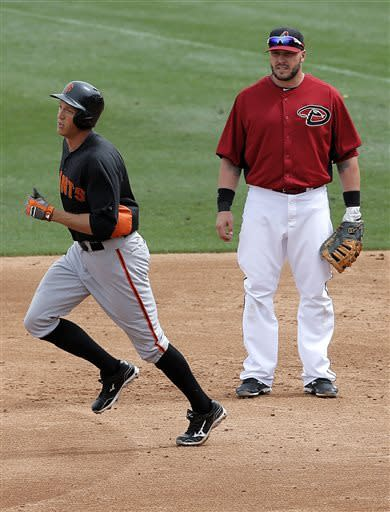 San Francisco Giants' Hunter Pence, left, rounds the bases after hitting a home run as Arizona Diamondbacks' Eric Hinske watches during the second inning of a spring training exhibition baseball game, Wednesday, March 27, 2013, in Scottsdale, Ariz. (AP Photo/Matt York)
