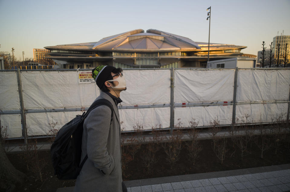 A man walks past the closed Tokyo Metropolitan Gymnasium, a venue renovated to be used in the rescheduled Tokyo Olympics, in Tokyo on Thursday, Jan. 21, 2021. The arena was used for the Tokyo 1964 Olympics. The postponed Tokyo Olympics are to open in just six months. Local organizers and the International Olympic Committee say they will go ahead on July 23. But it's still unclear how this will happen with virus cases surging in Tokyo and elsewhere around the globe. (AP Photo/Hiro Komae)