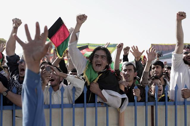 Afghan cricket fans celebrate runs by their team as they watch a match between Afghanistan and Kenya on a screen at the International Cricket Stadium in Kabul, Afghanistan, Friday, Oct. 4, 2013. War-weary Afghanistan achieved one of its finest sporting moments by qualifying for its first Cricket World Cup on Friday. (AP Photo/Rahmat Gul)