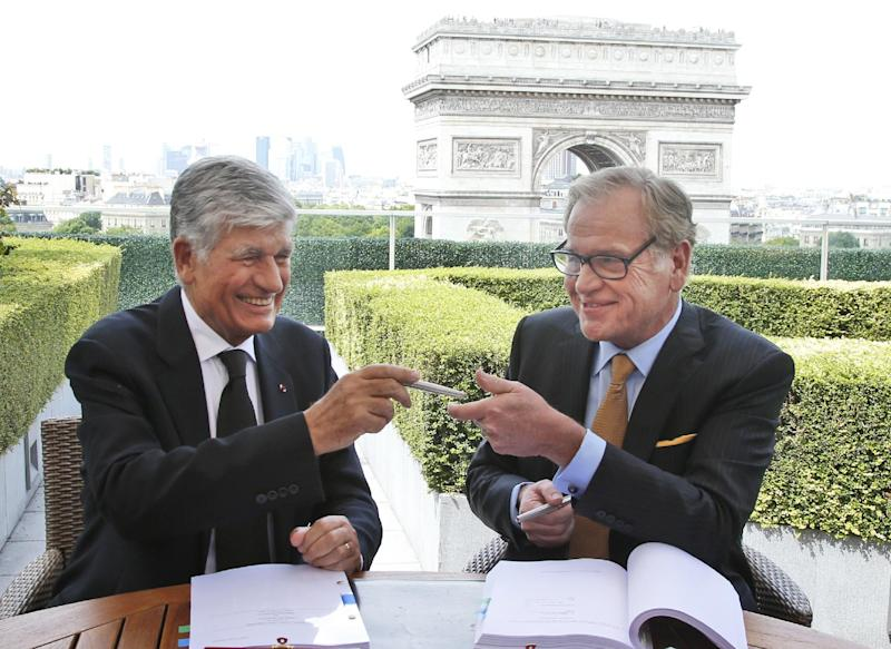 Maurice Levy, left, Chief Executive of French advertising group Publicis, and John Wren, head of Omnicom Group exchange a pencil during a joint signature prior to a news conference in Paris, France, Sunday, July 28, 2013. Publicis and Omnicom have announced merger plans to create the world's biggest advertising group . (AP Photo/Francois Mori)