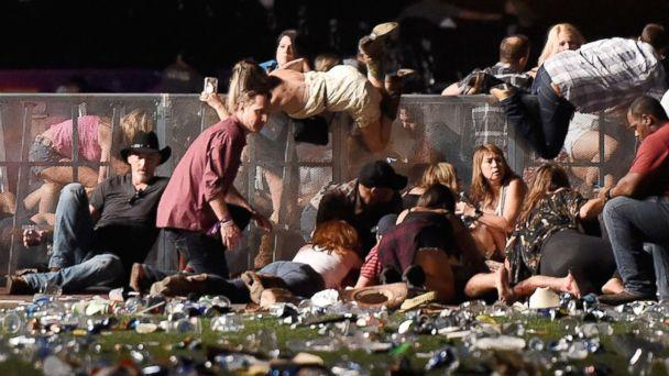 PHOTO: People scramble for shelter at the Route 91 Harvest country music festival, Oct. 1, 2017, in Las Vegas. (David Becker/Getty Images)