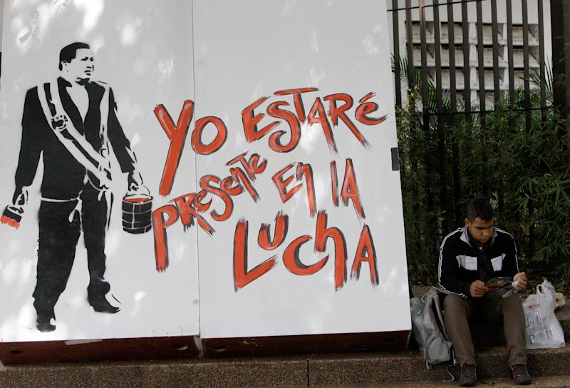 """A man reads a book as he sits next to a stencil mural depicting Venezuela's former President Hugo Chavez holding a bucket of red paint and a brush, that reads in Spanish """"I'll be present in the fight,"""" during the annual book fair in Caracas, Venezuela, Tuesday, March 19, 2013. (AP Photo/Fernando Llano)"""