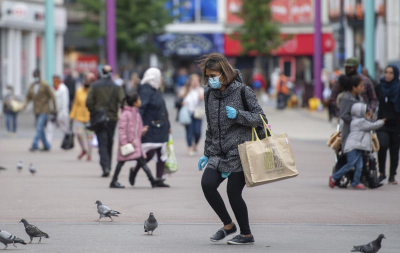 A shopper wearing a face mask on Humberstone Gate in Leicester, England, Monday June 29, 2020. The British government is reimposing lockdown restrictions in the central England city of Leicester after a spike in coronavirus infections, including the closure of shops that don't sell essential goods and schools. (Joe Giddens/PA via AP)