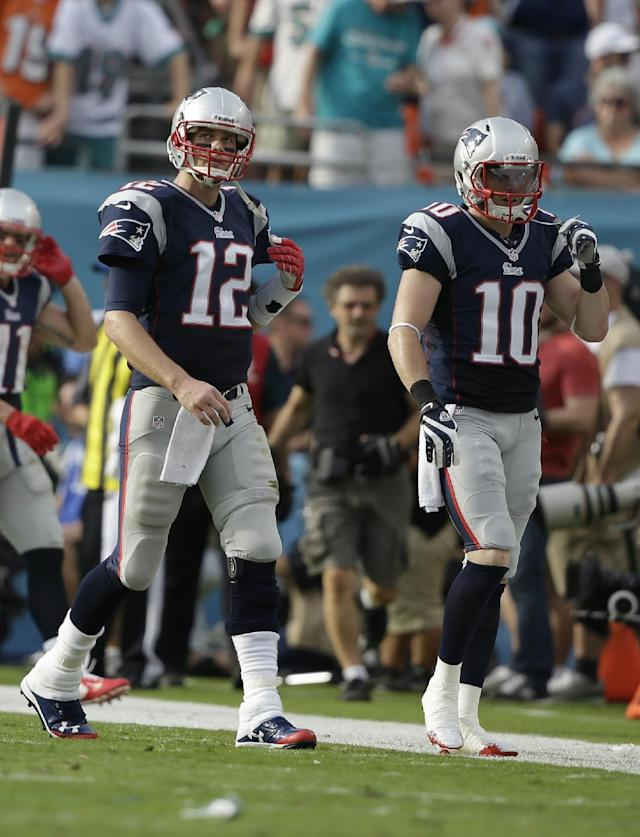 New England Patriots quarterback Tom Brady (12) and New England Patriots wide receiver Austin Collie (10) come off the field after a pass intended for Collie was intercepted by Miami Dolphins' Michael Thomas during the second half of an NFL football game, Sunday, Dec. 15, 2013, in Miami Gardens, Fla. The Dolphins defeated the Patriots 24-20. (AP Photo/Lynne Sladky)