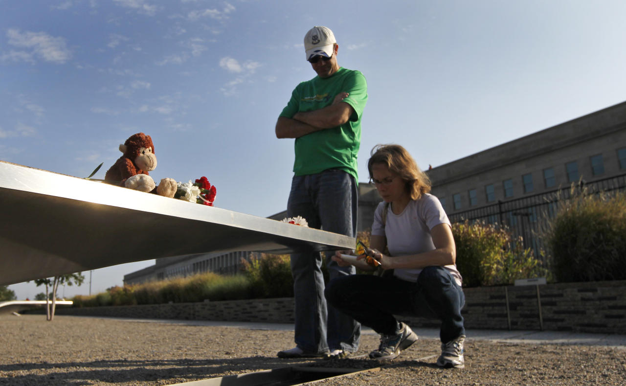 Visitors pause in front the Pentagon Memorial bench for Dana Falkenberg of University Park, Md., who was three when she died on American Airlines Flight 77 when it crashed into the Pentagon, ahead of the 10th anniversary of the Sept. 11 attacks, Saturday, Sept. 10, 2011, at the Pentagon in Washington. (AP Photo/Charles Dharapak)