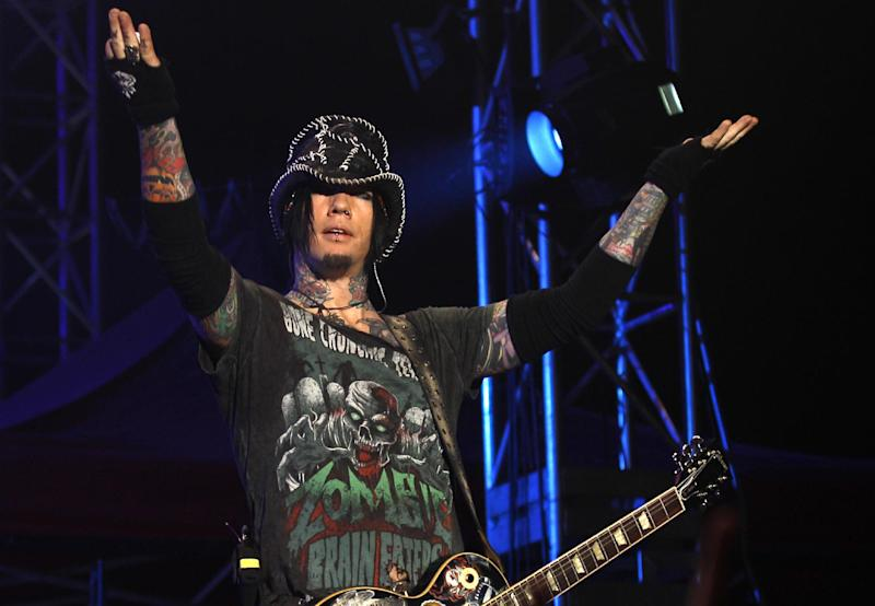"""FILE - In this Dec. 7,2012 file photo, Guns N' Roses guitarist DJ Ashba reacts to the crowd as he performs during a concert in Bangalore, India. Las Vegas police are investigating whether employees went too far after reportedly helping Ashba with an elaborate proposal. Ashba posted a photo on Instagram Saturday of himself and girlfriend Nathalia Henao wearing helicopter headgear thanking the Las Vegas police department for a private helicopter tour, saying it ended in a field at police headquarters, where he proposed amid roses and """"a bottle of the bubble stuff."""" (AP Photo/Aijaz Rahi, File)"""