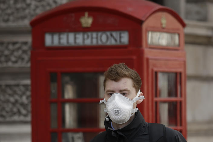 A man wearing a face mask walks past a traditional British red phone box just off Parliament Square in central London, Wednesday, March 11, 2020. A British government minister Nadine Dorries, who is a junior Heath minster has tested positive for the coronavirus and is self isolating. For most people, the new coronavirus causes only mild or moderate symptoms, such as fever and cough. For some, especially older adults and people with existing health problems, it can cause more severe illness, including pneumonia. (AP Photo/Matt Dunham)