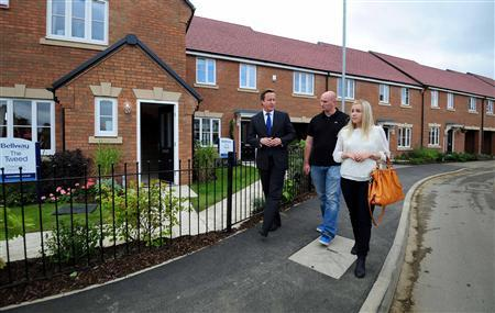 Britain's Prime Minister David Cameron speaks to first time buyers Kayleigh Groom and her partner Chris Day during a visit to Weston Favell in Northampton