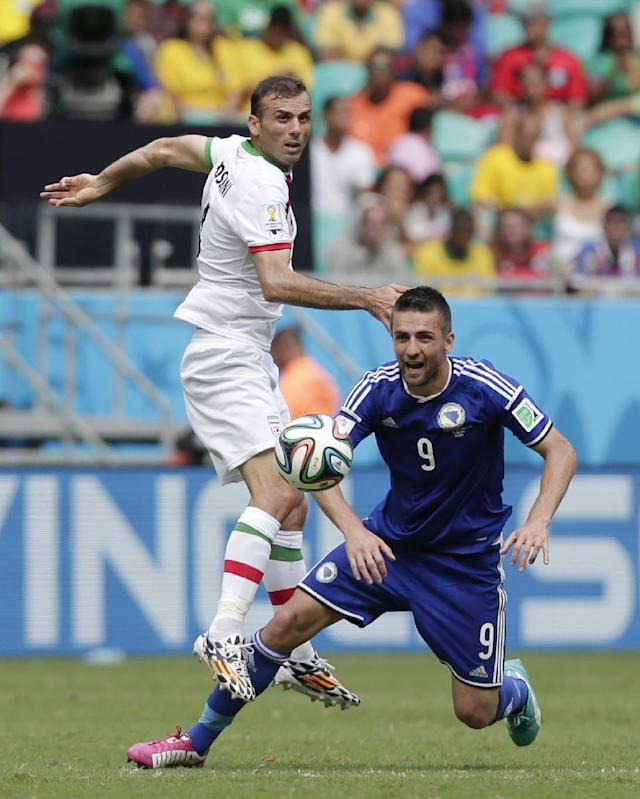Iran's Jalal Hosseini, left, fights for the ball with Bosnia's Vedad Ibisevic during the group F World Cup soccer match between Bosnia and Iran at the Arena Fonte Nova in Salvador, Brazil, Wednesday, June 25, 2014. (AP Photo/Marcio Jose Sanchez)