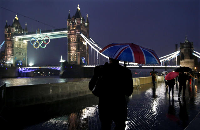 Pedestrians walk in the rain past the Tower Bridge displaying the Olympic rings Saturday, July 14, 2012 as London prepares for the 2012 Summer Olympics. (AP Photo/Jae C. Hong)