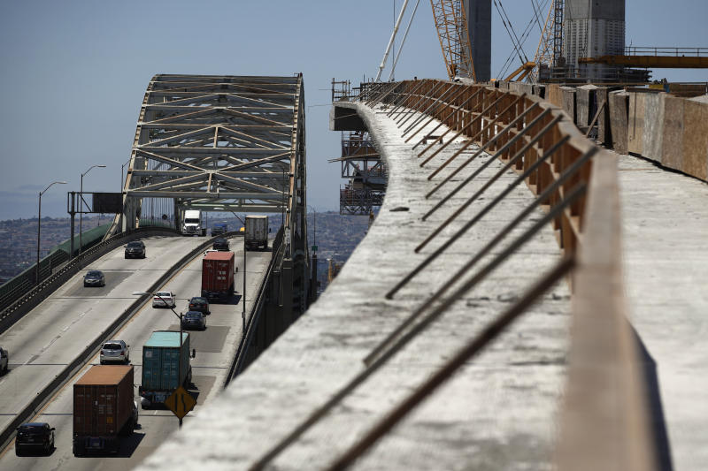 FILE - In this July 2, 2018, file photo, traffic moves on the old Gerald Desmond Bridge next to its replacement bridge under construction in Long Beach, Calif. President Donald Trump pronounced himself eager to work with Congress on a plan to rebuild America's crumbling roads and bridges, but offered no specifics during his State of the Union speech on what kind of deal he would back. (AP Photo/Jae C. Hong, File)