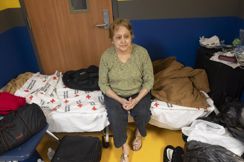 Dora Corso sits with all her belongings in the hallway of the North Myrtle Beach High School in North Myrtle Beach, S.C., Wednesday Sept. 4, 2019. Corso was evacuated from the beach front resort where she was living to the Red Cross shelter and has no plans for where to go after the storm passes. Residents of North Myrtle Beach are awaiting the arrival of Hurricane Dorian later today and through Thursday. (Jason Lee/The Sun News via AP)