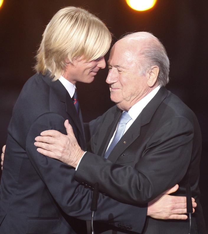 FILE - In this Monday, Jan. 9, 2012 file photo Italian soccer player Simone Farina, left, is embraced by FIFA President Sepp Blatter at the FIFA Ballon d'Or awarding ceremony in Zurich, Switzerland. In 2011, Italian defender Simone Farina turned down a fixer's offer of $261,500 to throw a game and reported it to police, setting off an investigation that led to scores of arrests. Despite being honored by FIFA, he found himself shunned by those in Italy who considered him a snitch. (AP Photo/Michael Probst, File)