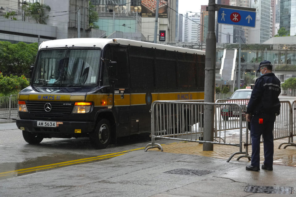 """A prison van arrives as a police officer stands guard for Tong Ying-kit's arrival at the Hong Kong High Court in Hong Kong Friday, July 30, 2021. Tong was convicted Tuesday of inciting secession and terrorism for driving his motorcycle into a group of police officers during a July 1, 2020, pro-democracy rally while carrying a flag bearing the banned slogan, """"Liberate Hong Kong, revolution of our times."""" Tong, 24, will be sentenced Friday, the court announced. (AP Photo/Vincent Yu)"""