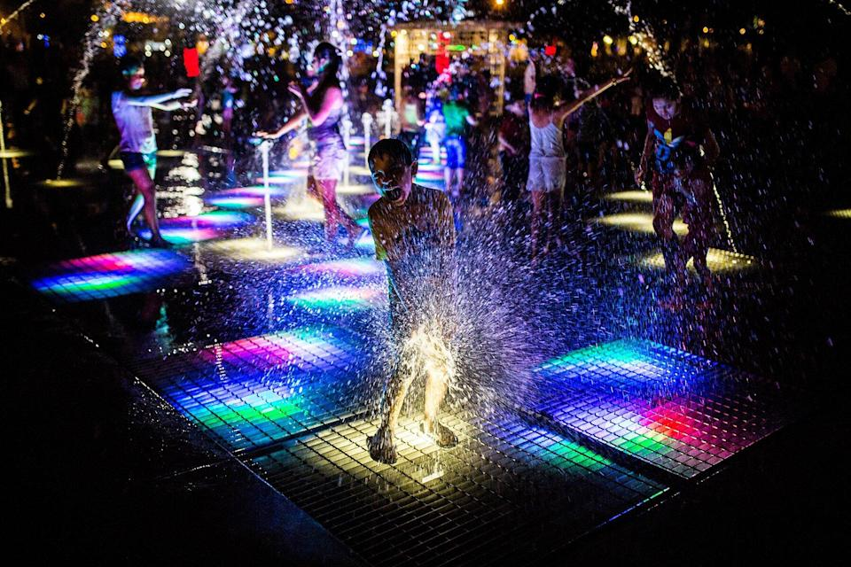 People play on an illuminated fountain at the Magic Water Circuit