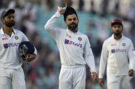 India's Virat Kohli, centre, leads his team off the pitch at close of play on day four of the fourth Test match at The Oval cricket ground in London, Sunday, Sept. 5, 2021. (AP Photo/Kirsty Wigglesworth)
