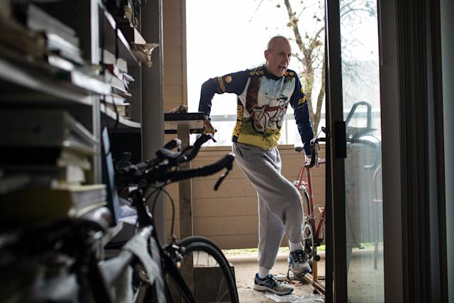 Chuck Yarling steps off his old triathlon bicycle, which he attached to a stationary bike stand on his patio outside his home in Austin.