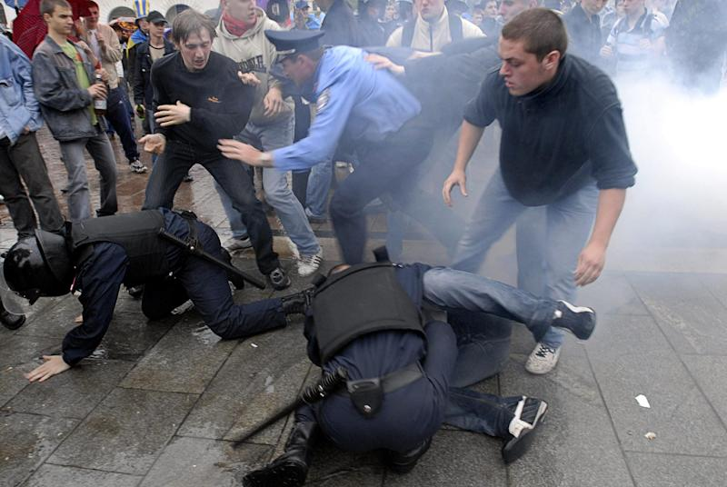 FILE - This file photo dated on June 14, 2006. shows Ukrainian police officers detaining soccer fans after Ukraine's soccer team's first ever appearance in the World Cup in Kiev, Ukraine. With a week to go until the Euro 2012 soccer tournament, Ukraine has been rocked by accusations of rampant racism after a British documentary showed thugs in one the Euro 2012 host cities violently beating dark-skinned soccer fans during a domestic league match. (AP Photo/Sergei Chuzavkov, file)