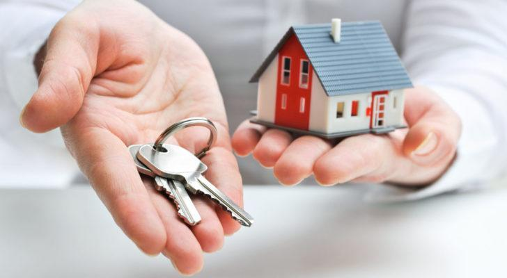 Hands holding a miniature house and keys
