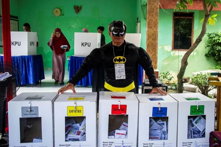 An election worker dressed in a superhero costume waits for voters. 'Indonesians have embraced their own electoral power, especially younger voters,' says Southeast Asia expert Bridget Welsh