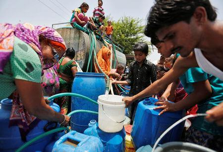 Local residents fill their empty containers with water from municipal corporation tanker on a hot summer day in Ahmedabad, India May 11, 2016. REUTERS/Amit Dave